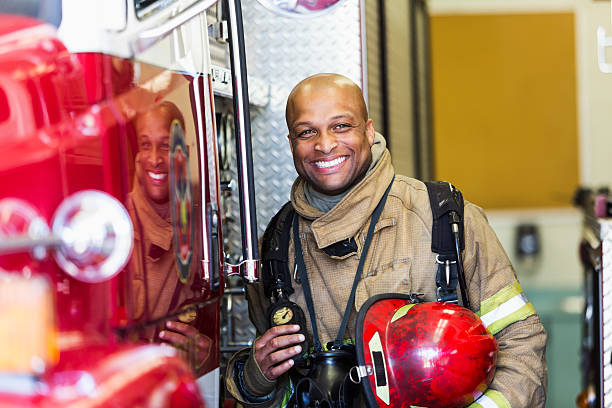african american fire fighter standing next to truck - firefighter stock photos and pictures