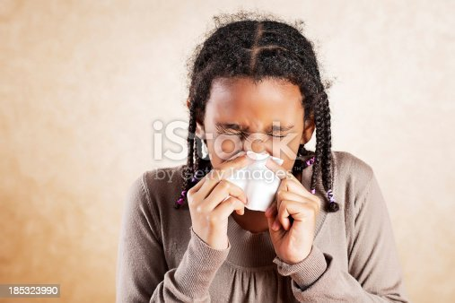 istock African American girl blowing her nose. 185323990