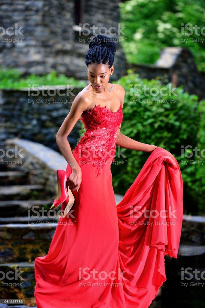 8debdfb4970e7a African American meisje in een rode jurk met rode schoenen in zijn hand  poseren in het