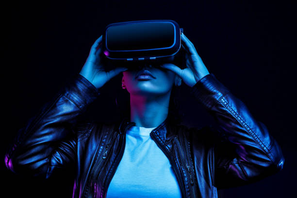 African american girl in vr glasses, watching 360 degree video with virtual reality headset isolated on black background, illuminated by neon lights African american girl in vr glasses, watching 360 degree video with virtual reality headset isolated on black background, illuminated by neon lights training equipment stock pictures, royalty-free photos & images