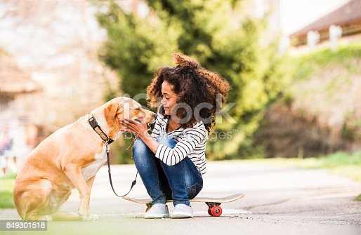 istock African american girl outdoors on skateboard with her dog. 849301518