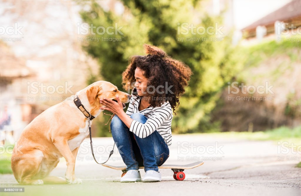 African american girl outdoors on skateboard with her dog. stock photo