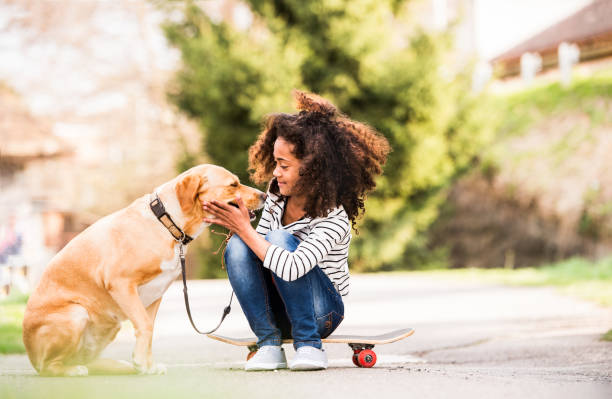african american girl outdoors on skateboard with her dog. - one girl only stock pictures, royalty-free photos & images