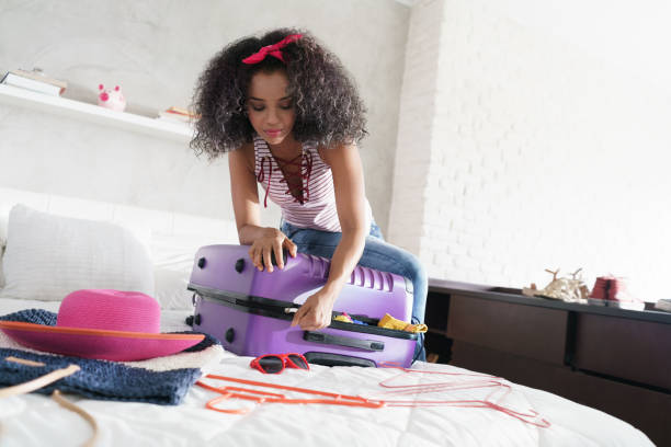 African American Girl Preparing Baggage For Vacation And Travel stock photo