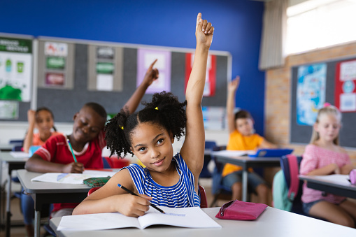 African american girl raising her hands while sitting on her desk in the class at school. school and education concept