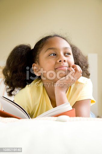 African American girl reading book in bed