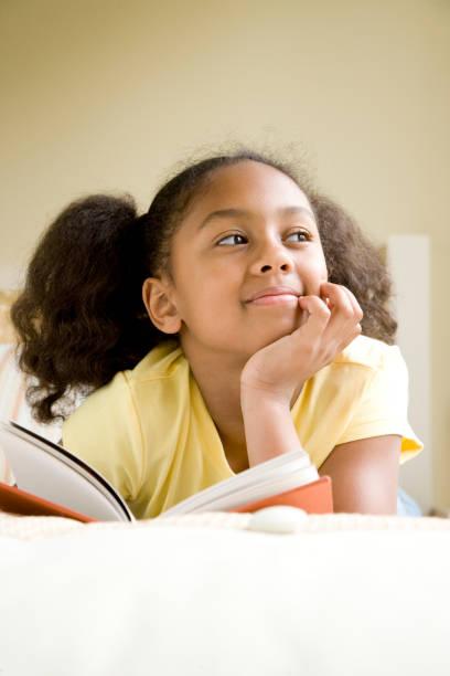 african american girl reading book in bed - mano sul mento foto e immagini stock