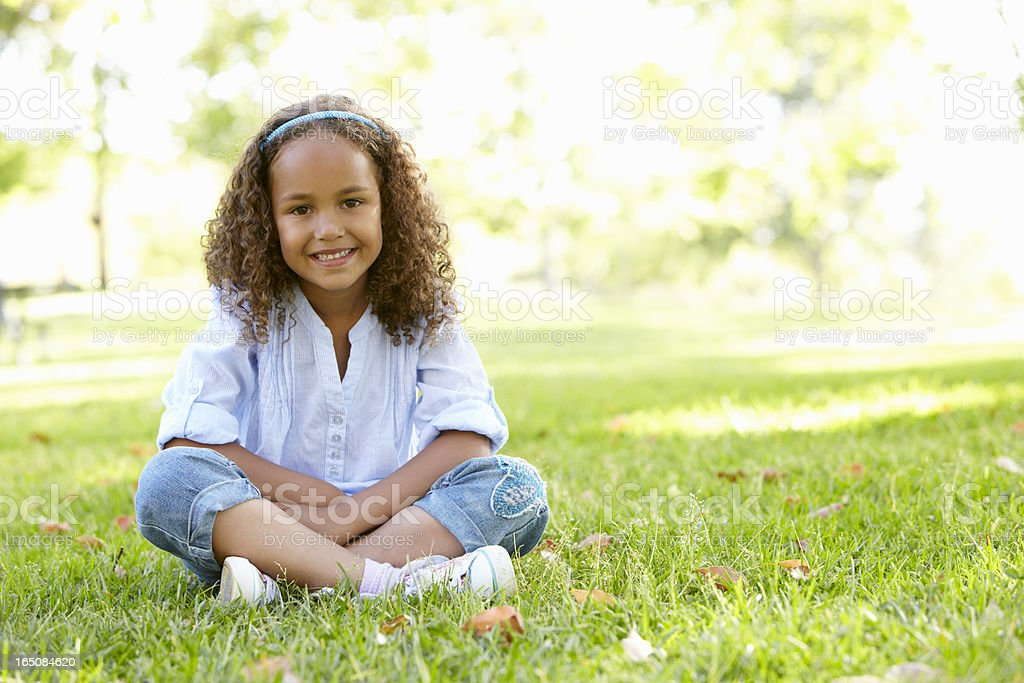 African American Girl Sitting In Park stock photo