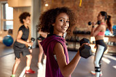 istock African american girl smiling at camera while exercising using dumbbell in gym together with female trainer and other kids. Sport, healthy lifestyle, physical education concept 1247981111