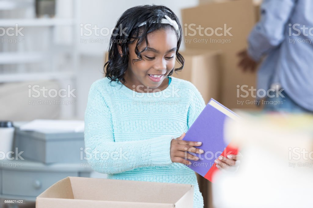African American girl unpacks in her new home stock photo
