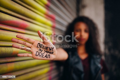 Closeup of the hand of an African American girl with an inspirational message written on it in permanent marker