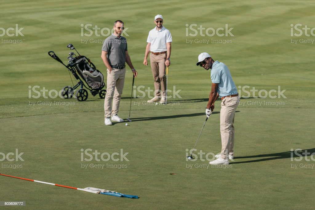 african american golfer take a shot with golf club while his friends standing behind on green stock photo