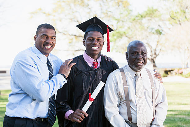 African American graduate with father and grandfather stock photo