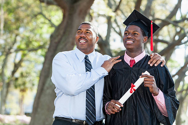 African American graduate with proud father. stock photo