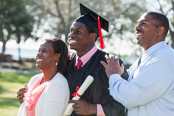 African American graduate with proud parents stock photo