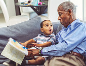 istock African American grandchild and grandfather read a book together at home 1265056799