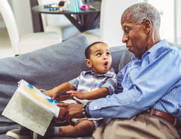 African American grandchild and grandfather read a book together at home stock photo