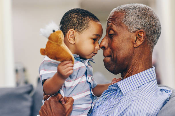 African American grandfather and grandson face to face stock photo