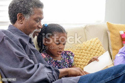 She is sitting on the sofa with her granddad learning to read and he is patiently listening