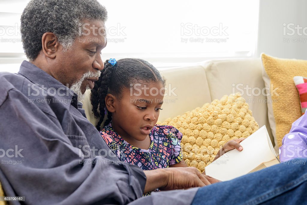 African American grandfather listening to girl read book stock photo