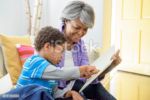 The young boy is pointing to the book and his grandma is helping him to read