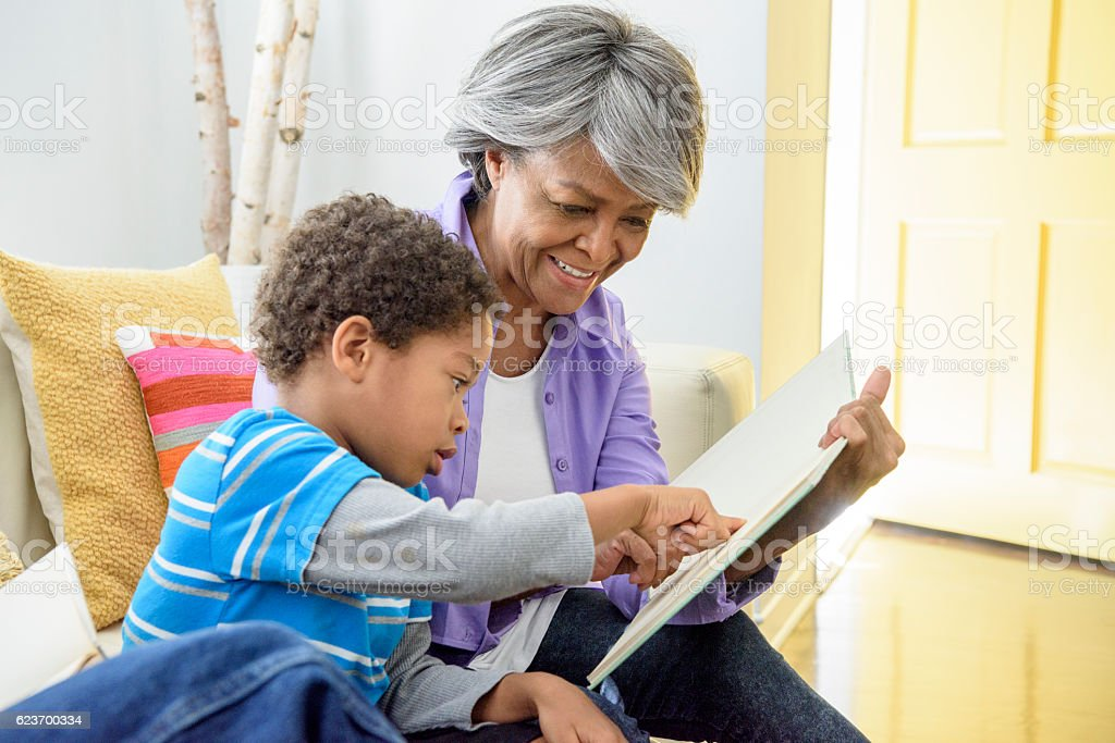 African American grandmother showing book to grandson, smiling stock photo