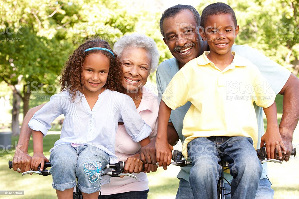 African American Grandparents With Grandchildren Cycling In Park royalty-free stock photo