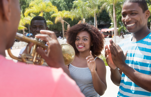 istock African american group enjoy music of musician with trumpet 675715316