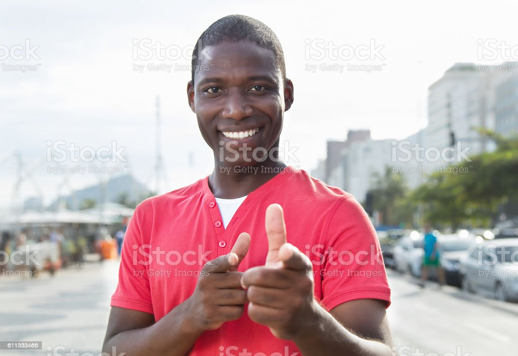 African american guy in a red shirt pointing at camera stock photo