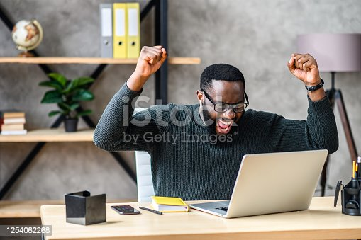 Success at work, good deal. African-American guy looks at the laptop screen, screams excitedly and raises his fists in a victory gesture