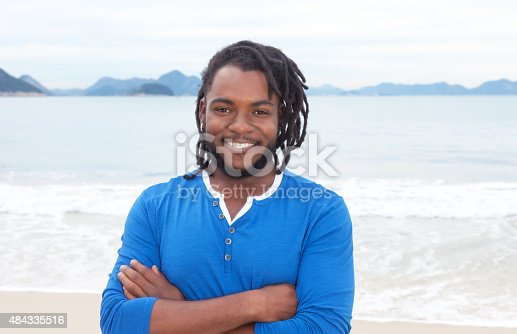 182677415 istock photo African american guy with dreadlocks and crossed arms at beach 484335516