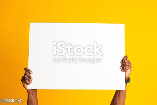 1159989540 istock photo African american hands holding big banner white sheet of paper 1209051147