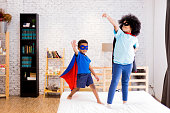 African American happy and confident young kids playing \n and dressing up as superhero together in bedroom