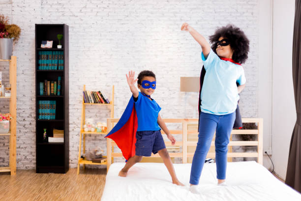 afrikanischer amerikaner glücklich und zuversichtlich kleine kinder spielen und verkleiden sich als superheld zusammen im schlafzimmer. - spiel des wissens stock-fotos und bilder