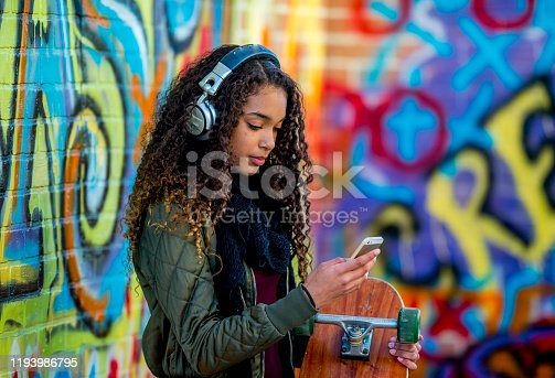 A female African American hipster student, with long dark curly hair, stands in front of a brick wall covered in graffiti.  She is dressed casually and wearing a fall coat.  The student has headphones on as she holds her skateboard in one hand and her cell phone in the other.  She is scrolling through her music selection before heading off on her skateboard to meet friends.