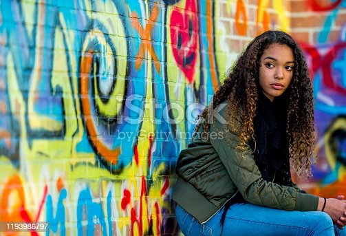 A female African American hipster student, with long dark curly hair, sits against a brick wall covered in graffiti.  She is dressed casually and wearing a fall coat as she holds her cell phone in her hand.