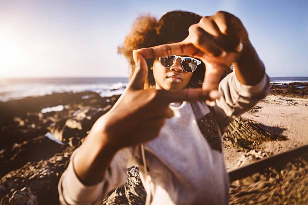 african american hipster teenager am strand, mit finger frame - dynamische posen stock-fotos und bilder