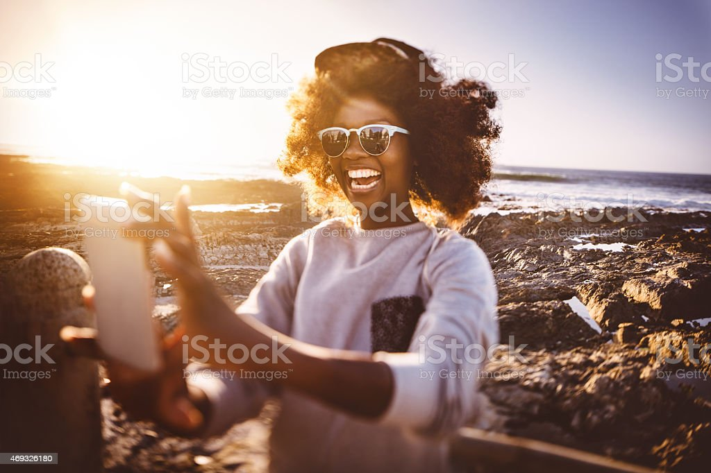 African American hipster teen girl taking selfie at the beach stock photo