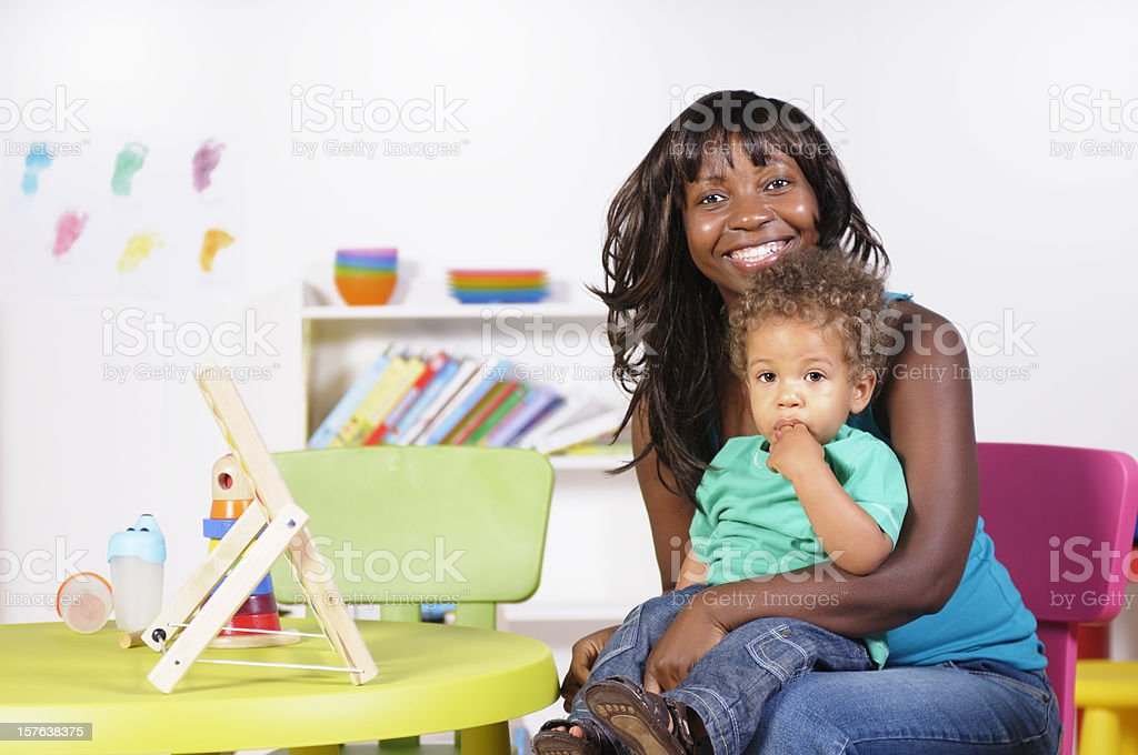 African American Holding Baby/ Toddler In A Nursery Setting stock photo