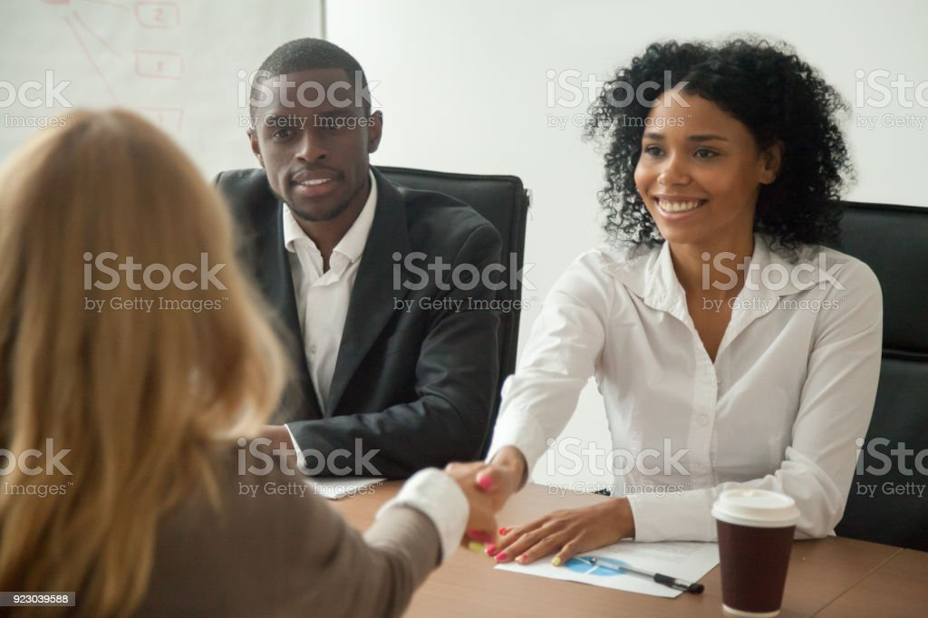 African american hr team welcoming female applicant at job interview stock photo