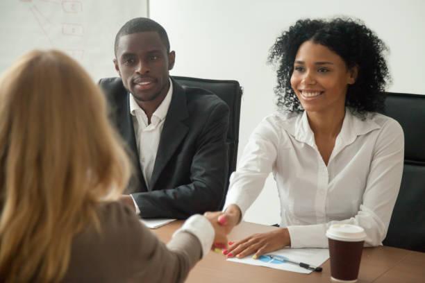 african american hr team välkomnande kvinnliga sökanden på anställningsintervju - new job bildbanksfoton och bilder