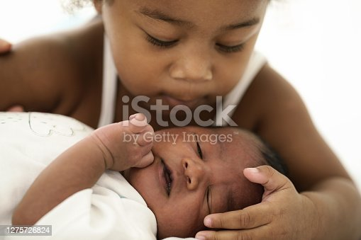 african american infant baby lying on bed while sister watching