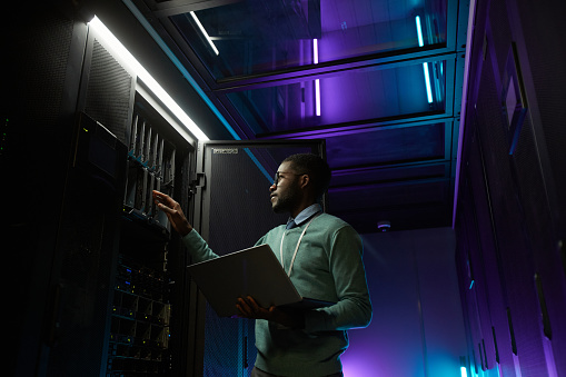 Low angle portrait of young African American data engineer working with supercomputer in server room lit by blue light and holding laptop, copy space