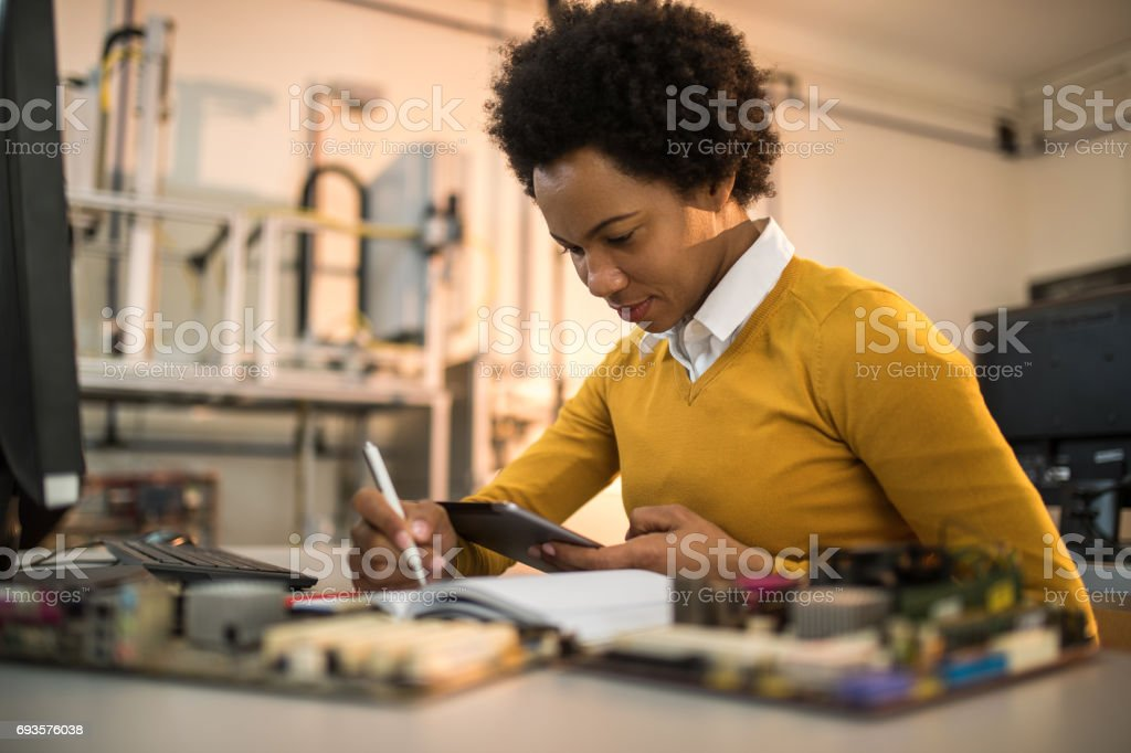 African American IT technician taking notes while using digital tablet. stock photo