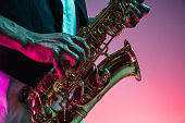 African American handsome jazz musician playing the saxophone in the studio on a neon background. Music concept. Young joyful attractive guy improvising. Close-up retro portrait.
