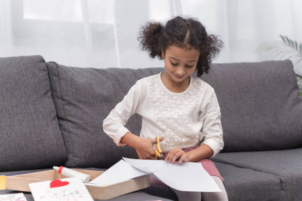 african american kid cutting paper for greeting card on mothers day stock photo