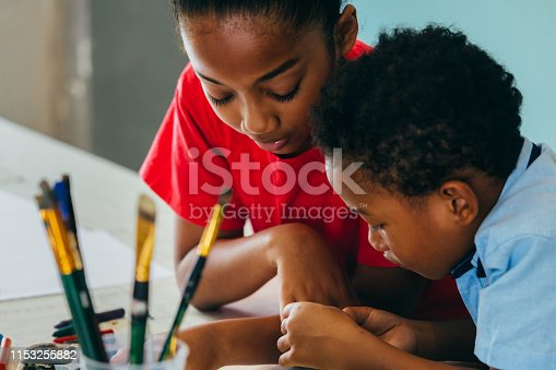 Closeup of elementary African American kids creatively drawing and painting with brushes and crayon - children creative education concept