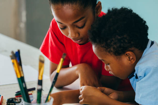 African American kids drawing and painting Closeup of elementary African American kids creatively drawing and painting with brushes and crayon - children creative education concept craft stock pictures, royalty-free photos & images
