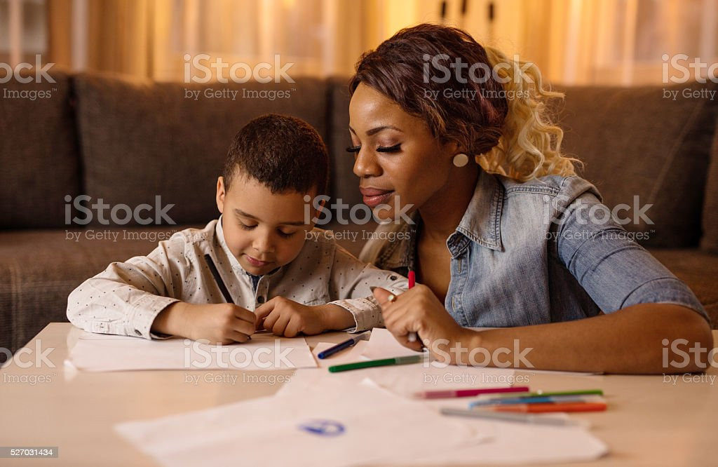 African American little boy sketching with his mother at home. stock photo