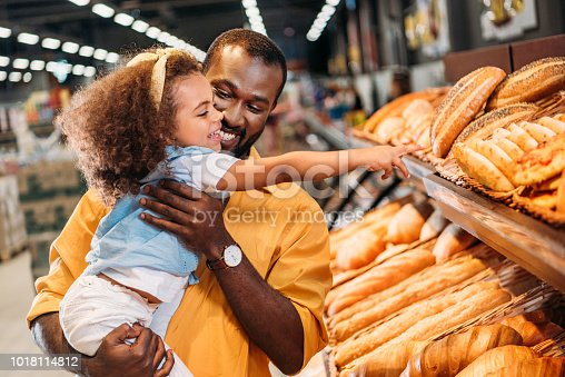 african american little child pointing by finger at pastry to father in supermarket